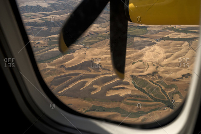 View of hilly landscape through plane window