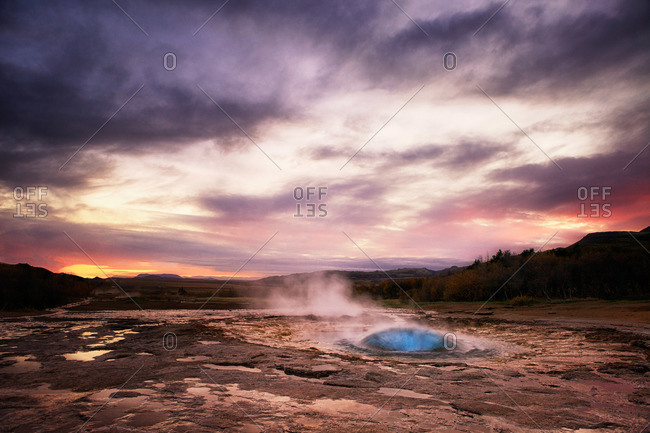 Geyser steaming in Iceland at sunset