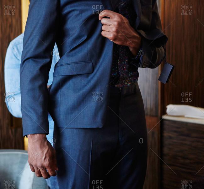 Stylist adjusting fit of man's suit coat