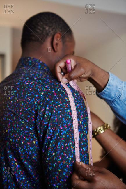 Tailor measuring a man's sleeve length