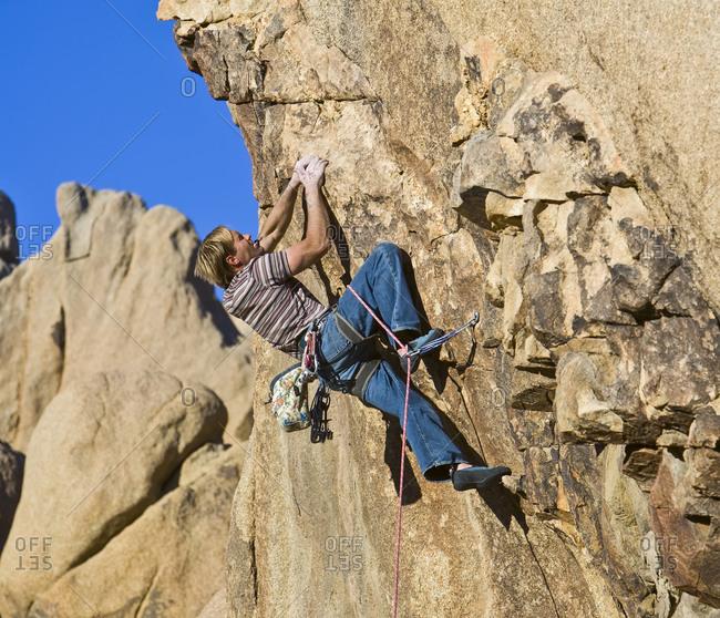 Man in difficult rock climb