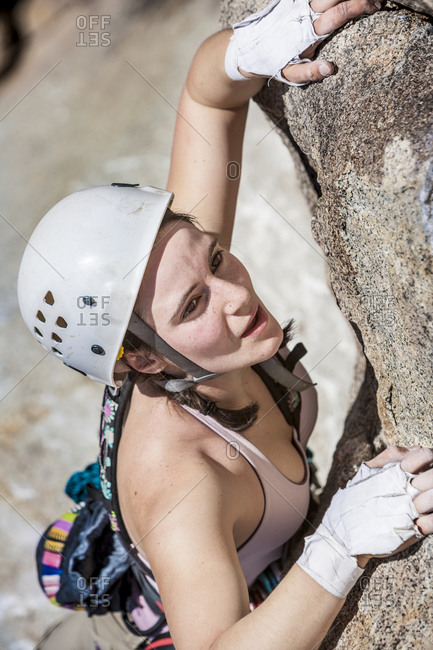 Female climber scaling rock surface