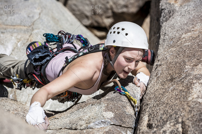 Female climber scaling up a crack