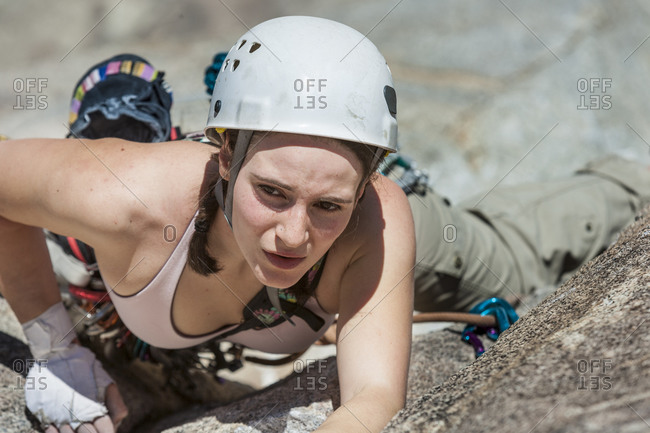 Female climber scaling crack in mountain