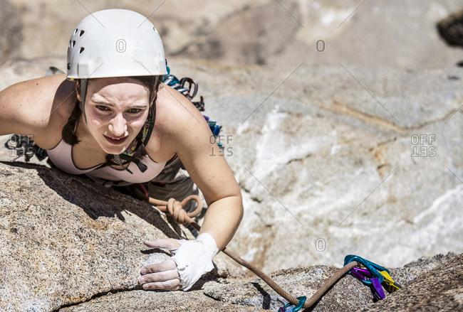 Female climber scaling crack in cliff