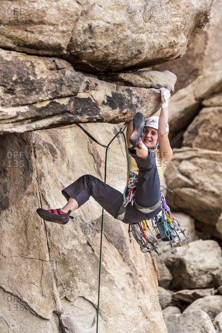 Female climber dangles from overhang of cliff