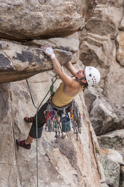 Female climber dangles from cliff overhang