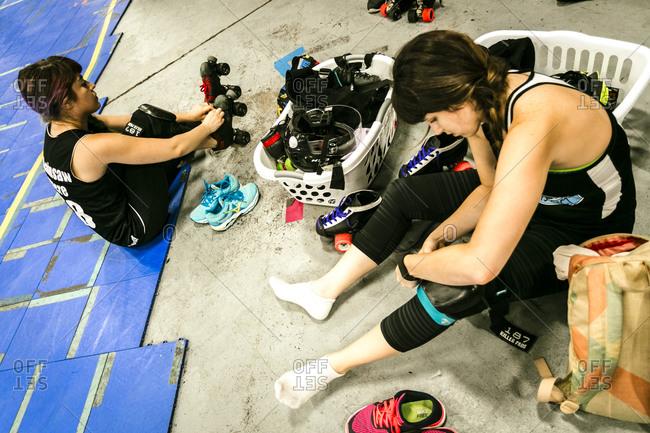 Roller derby teammates putting on gear