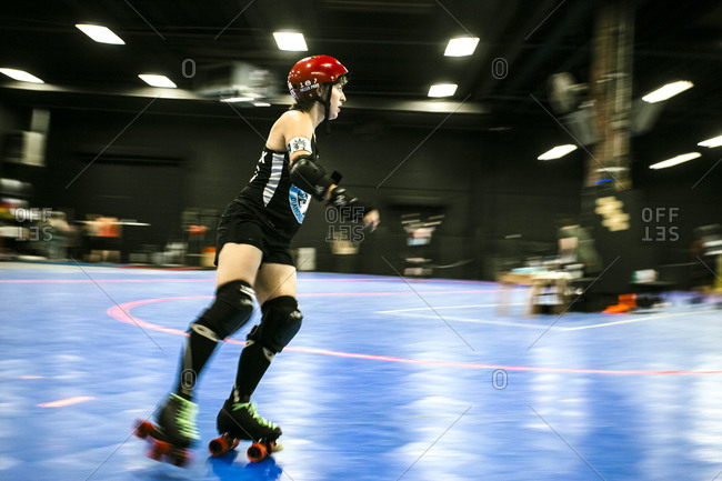 Roller derby competitor skating in rink