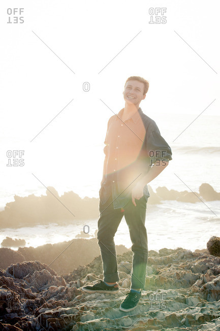 A young man smiles on a sun-drenched beach