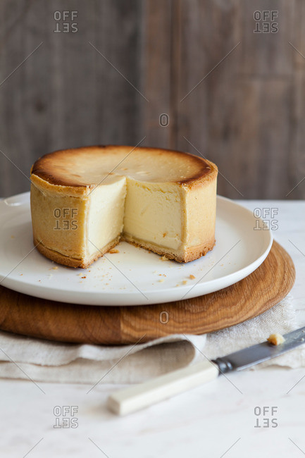 A thick cheesecake with a slice removed