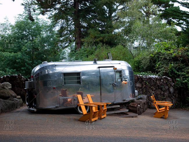 Marin County, California, USA - February 12, 2014: Airstream camper and wooden chairs at a campsite