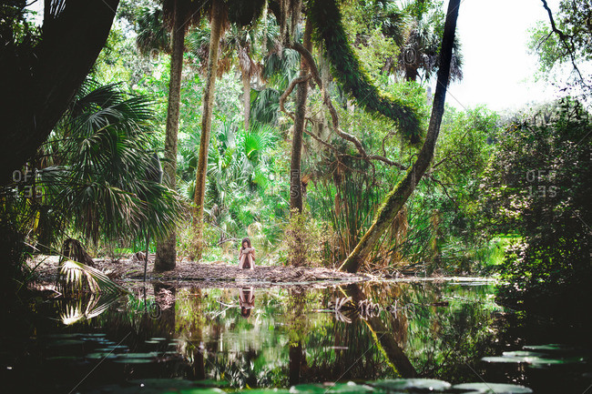 A girl writes in a notebook by a swamp