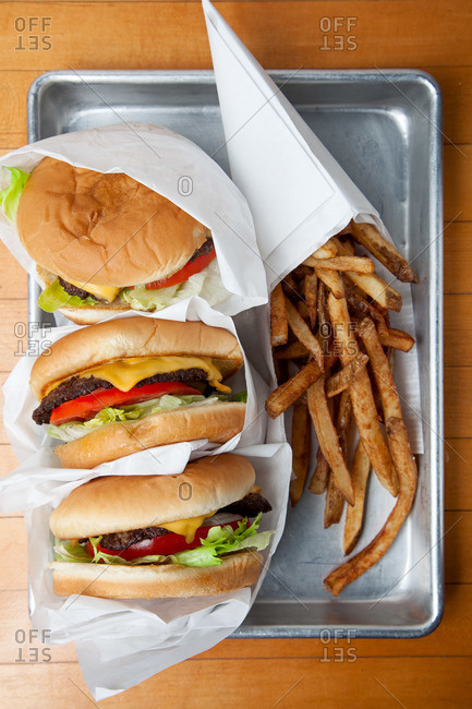 Three cheeseburgers and french fries in San Antonio, TX.