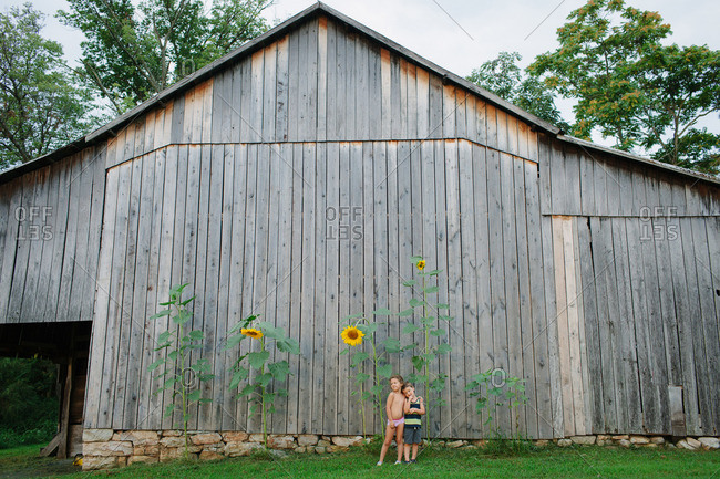 A brother and sister stand in front of towering sunflowers