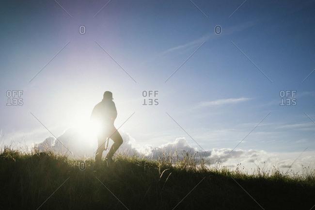 Man walking across a grassy hill