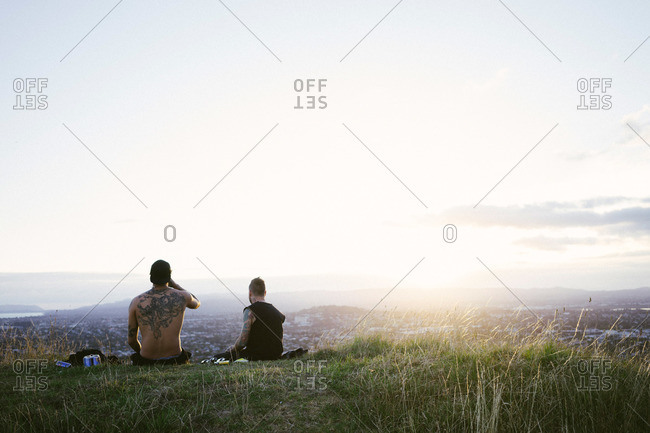 Auckland, New Zealand - February 19, 2015: Two men sitting on a mountainside overlooking Auckland, New Zealand
