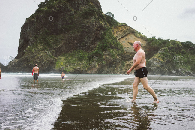 Auckland, New Zealand - February 20, 2015: People in the surf on Piha Beach in Auckland, New Zealand