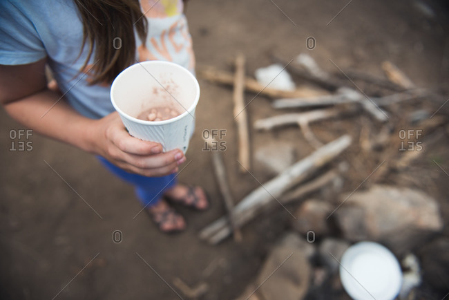 A child holds a cup of hot chocolate by a camp fire