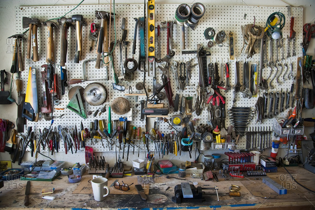 Tools organized on a pegboard above a home workbench