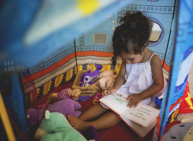 Girl reading inside a rocket ship tent