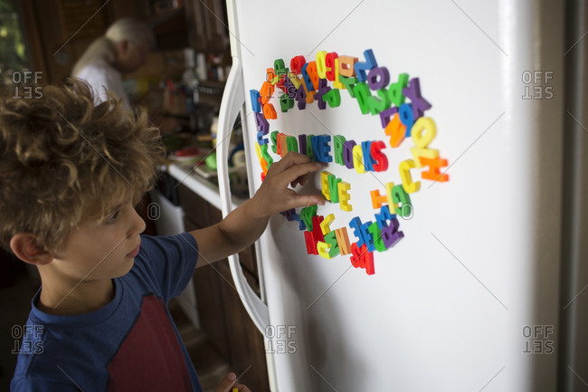 Boy spelling out words with fridge magnets