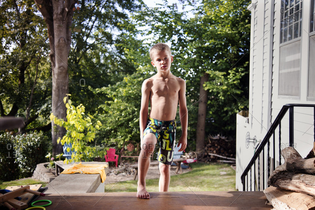 Young boy in swim shorts climbing porch steps