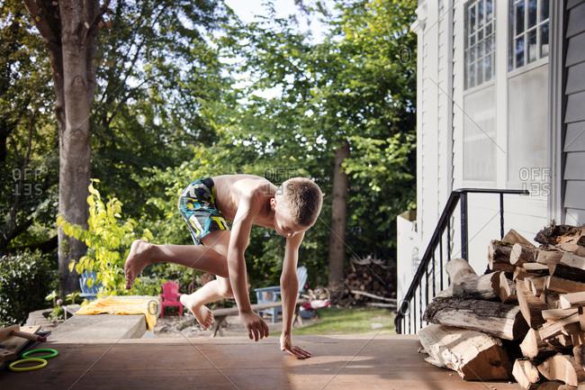 Boy in swim shorts jumping onto porch