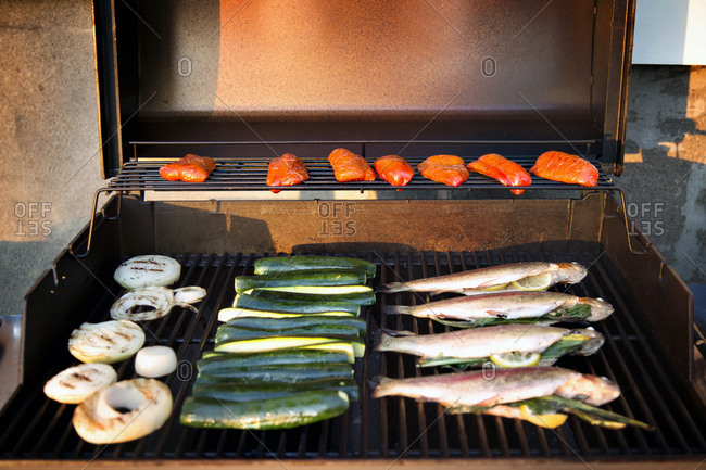 Stuffed fish and veggies on a grill