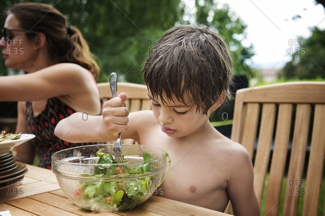 Boy at picnic table poking salad with fork