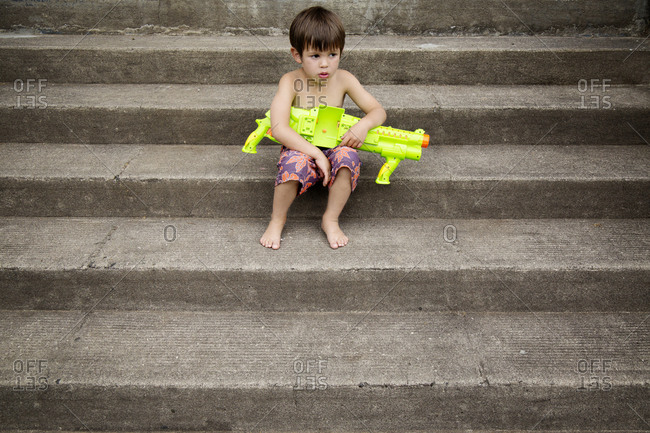 Boy sitting on steps with a water gun