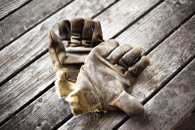 Well worn work gloves on wood boards
