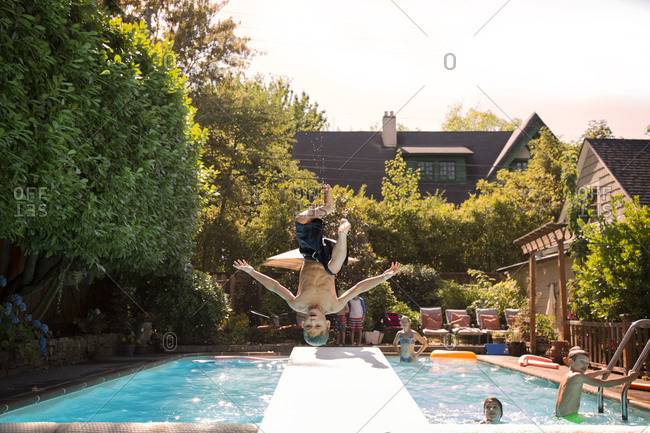 Boy mid flip jumping into swimming pool