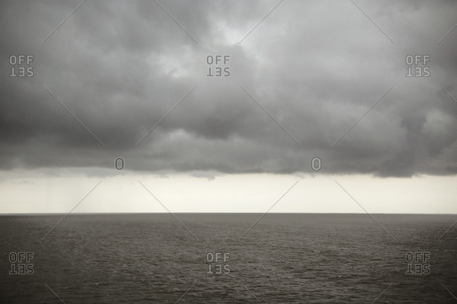 Still ocean water under rain clouds