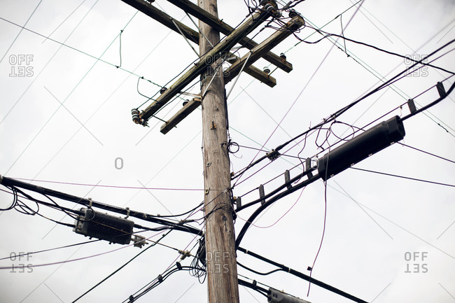 A telephone pole crowded with lines