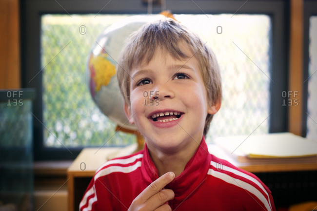 Portrait of young boy laughing in a classroom
