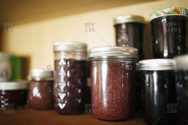 Various jars of preserves on kitchen shelf