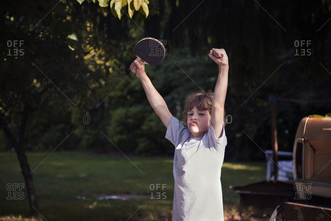 Young boy with ping pong paddle celebrating