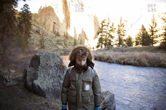 Young boy in parka huddled by river bank