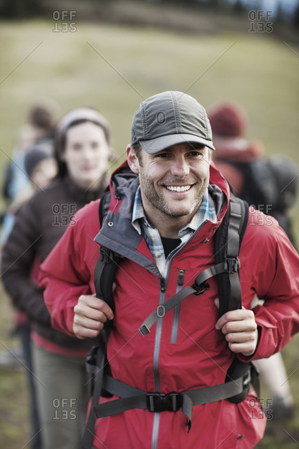 Man smiling as he leads friends on wilderness hike