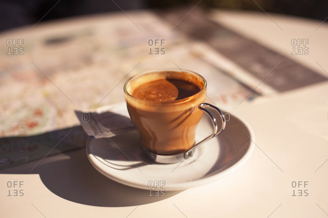 Cup of espresso on cafe table in morning light