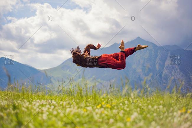 Woman midair doing leap in mountain setting