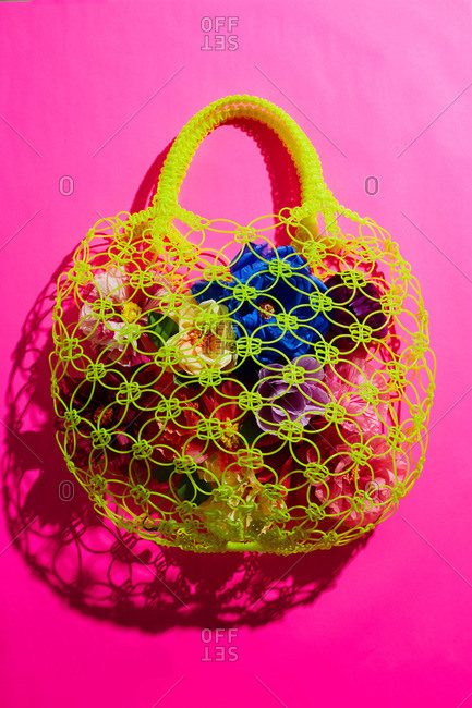Hand crafted paper flowers in plastic netted tote bag on hot pink paper background