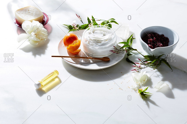 Natural beauty products, white peony blossoms and ceramics on white marble surface