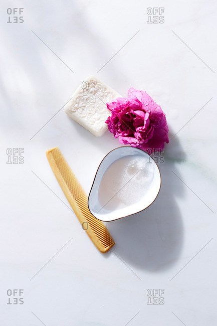 Natural soap, pink peony blossom, comb and bowl on white marble surface