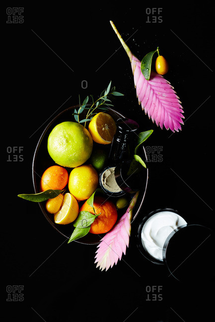 Natural face cream and face mask in black ceramic bowl with citrus fruits and tropical ginger flowers on black background