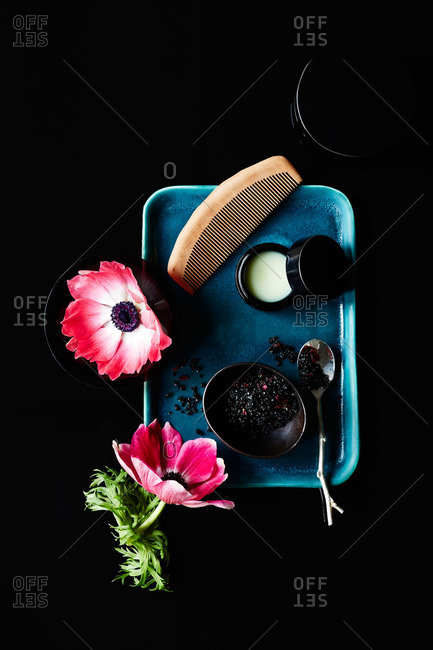 Natural bath soak, lip balm, black ceramic bowls, blue ceramic tray, comb and pink anemone flowers on black background