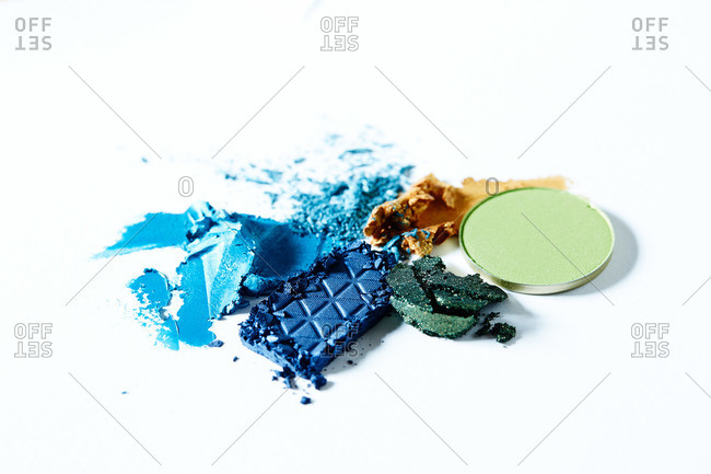 Smeared blue, gold and green eye shadows on white surface
