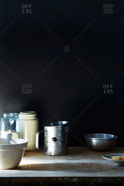 Vintage flour sifter, jars, bowls and cookie on rustic wood surface with black background