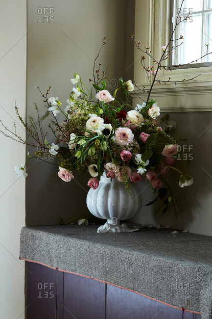Flower arrangement of anemones, peones and branches in white vase under window